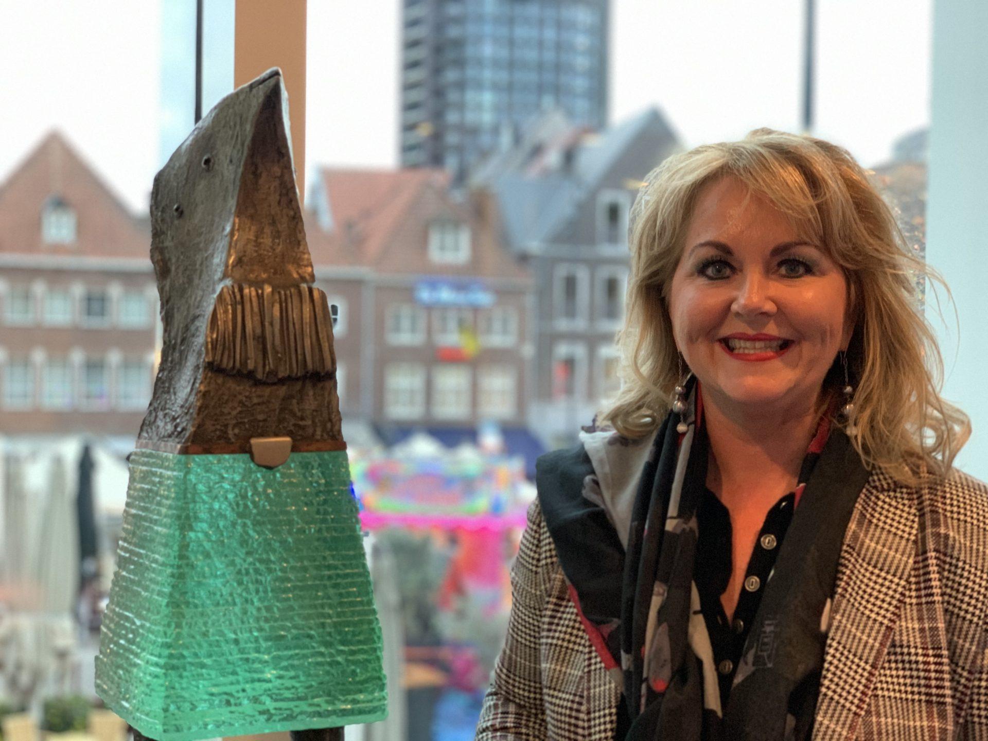 Portretfoto Lianne met groot kunstwerk brons glas bij Maaspoort Venlo