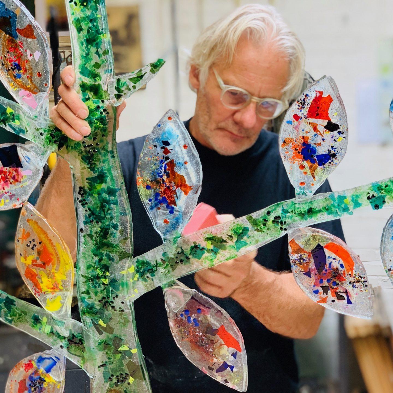 Sjaak werkt aan wandobject genogram familie glas